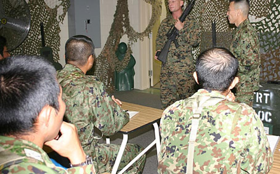 Staff Sgt. Jeffery Wagner, from Ashley, Mich., a tactics instructor with 3rd Marine Logistics Group, explains the capabilities of the M-16A4 to Japan Ground Self-Defense troops.