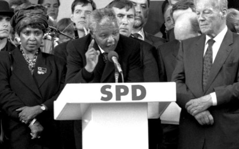 Winnie Mandela and former West German chancellor Willy Brandt listen as Nelson Mandela speaks at Bonn, Germany, in June, 1990.