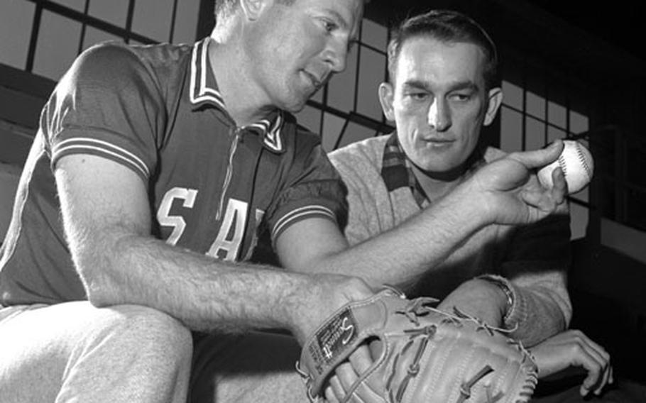 New York Yankees pitcher Whitey Ford gives pointers to Johnny Ross of the Darmstadt Comets during the USAFE clinic at Wiesbaden. Ross was the winningest lefthander in the Germany Conference over the previous three years; at one point in 1965, he won five games within eight days.