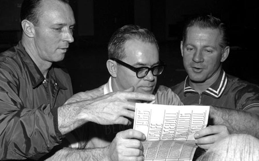 Left to right, Yankees coach Jim Hegan, Wiesbaden Air Base gym director Ben Royster and Whitey Ford look over a schedule for the clinic.