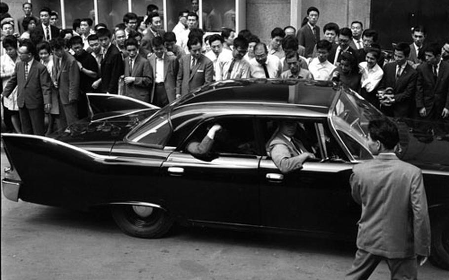 Astronaut John Glenn tours a Tokyo department store with his family, then departs in a car that takes the era's obsession with tailfins to a new height.