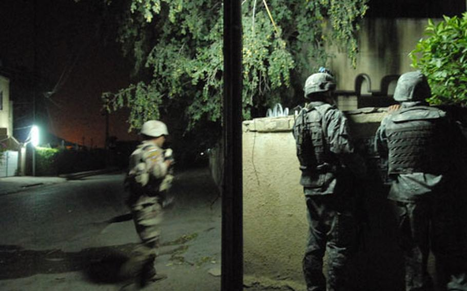 An American soldier (center) and his interpreter (right) peek over a wall Sunday in the Saydiyah area of Baghdad, Iraq, while helping Iraqi Army soldiers (left) look for a black car connected to an attempted killing. The incident was the second in as many days, marring an otherwise successful peace in the area.