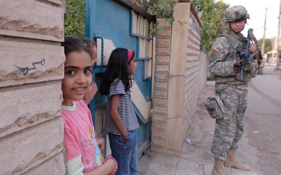 An Iraqi girl turns to check out the camera while Spc. Justin Jelley, 23, of Tulsa, Okla., jokes with another Iraqi girl Sunday in the Saydiyah neighborhood of Baghdad. For soldiers, the presence of children is a reassuring sign that the streets are safe here, in contrast to areas within earshot that are being torn apart by violence.