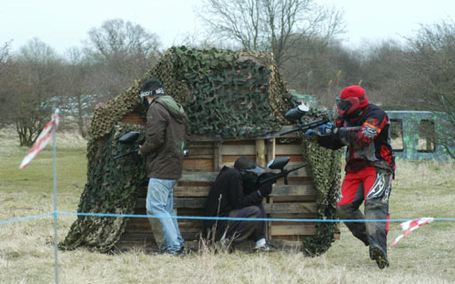 RAF Mildenhall's Tech. Sgt. Myron Grant, in red-and-black jumpsuit, takes out two opponents in a match against a RAF Menwith Hill team in a paintball tournament. Teams from six UK bases were represented in Saturday's event.