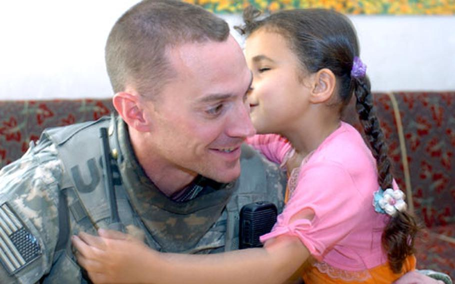 Noor Taha Najee gives 1st Lt. Michael Kendrick, platoon leader of 2nd Platoon, 1st Battalion, 30th Infantry Regiment a goodbye kiss near the end of a visit to her house in al Buaytha, Iraq.