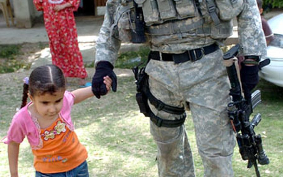Five-year-old Noor gives Kendrick a tour of her yard during a visit the soldier made to her house in al Buaytha, Iraq.