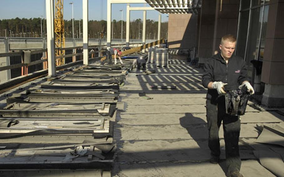 A construction worker from the contractor Lanzenstiel transports tar used to seal the membrane on a portion of the Kaiserslautern Military Community Center roof Tuesday at Ramstein Air Base, Germany. Phase 1 of a four-step plan to fix the poorly constructed roof is under way.