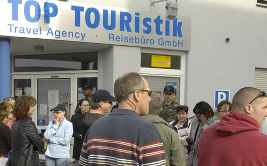 Dozens of Americans wait outside the Top TOURistik travel agency in Einsiedlerhof, Germany, on Tuesday eager to receive tickets for the cruise they signed up for.