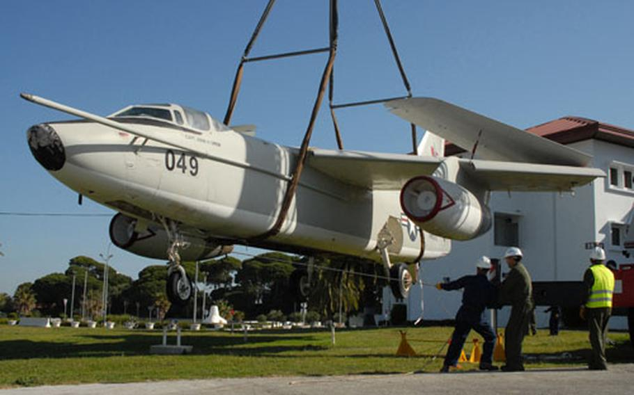 """Naval Station Rota Naval Facilities Engineering Command Europe and Southwest Asia Europe Field Office Rota employees hold ropes on a Douglas EA-3B """"Skywarrior"""" aircraft as it is hoisted from its display spot in front of Rota's Bachelor Officers Quarters."""