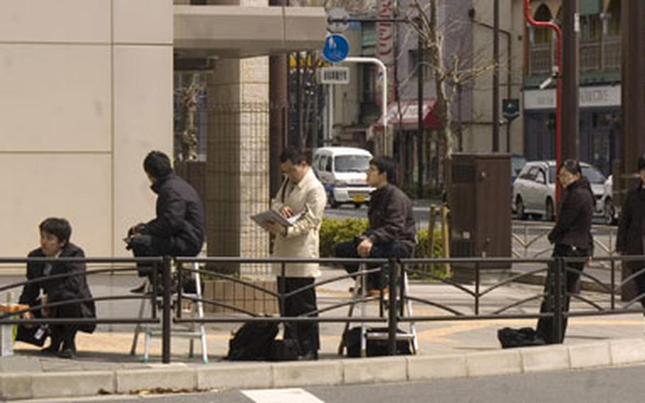 Japanese media representatives wait outside the Yokosuka Naval Base, Japan, main gate Wednesday in hopes of getting photos of a U.S. sailor who was questioned by Japanese police investigating the stabbing death of a taxi driver.