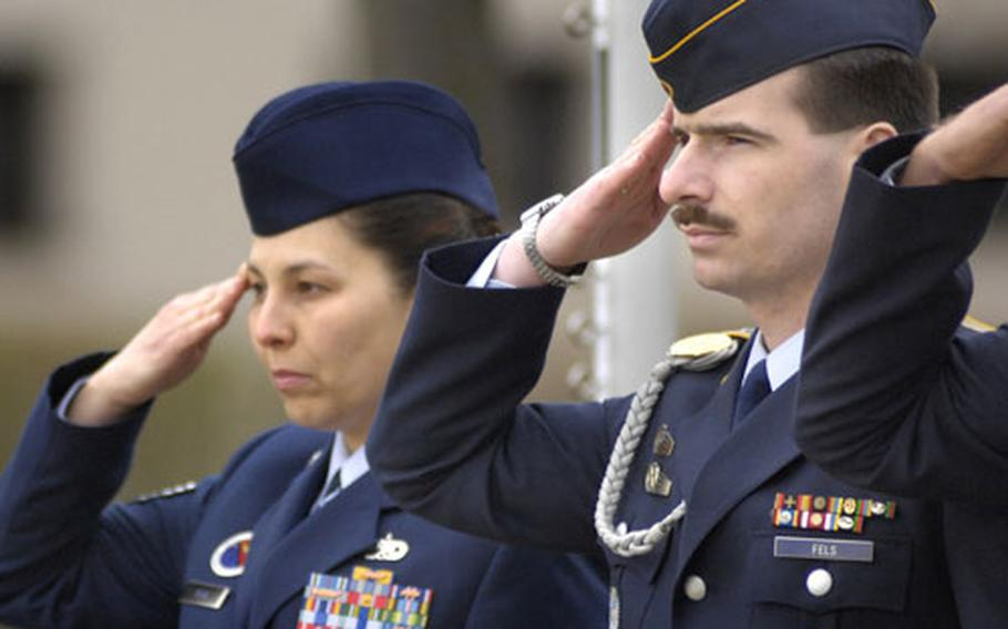 Master Sgt. Holger Fels, 35, an exchange student from the German Air Force, salutes alongside Tech. Sgt. Treena Merk, a Kisling NCO Academy instructor, as the U.S. and German flags are lowered during a retreat ceremony Thursday at Kaupan Air Station near Kaiserslautern.