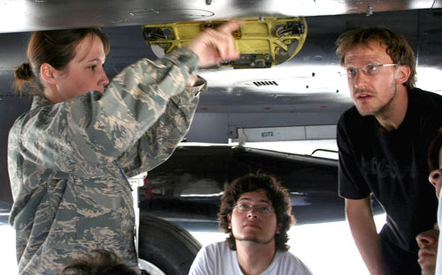 Master Sgt. Martha Watt, from the Mountain Home, Idaho-based 391st Fighter Squad, explains the mechanics of an F-15 Eagle to electrical engineering students from La Universidad de Chile Thursday at the air show.
