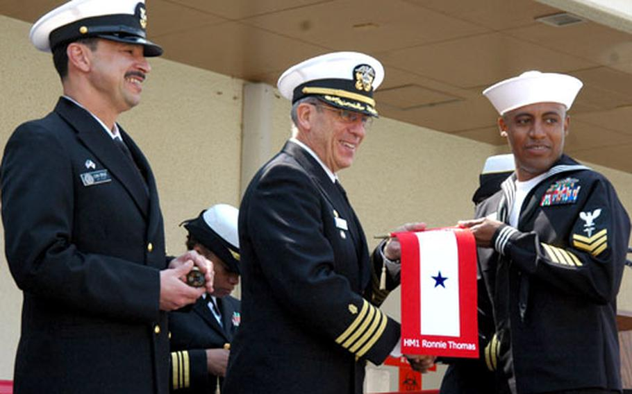 Capt. Michael Krentz, center, commanding officer of Naval Hospital Yokosuka, presents a blue star service flag to Petty Officer 1st Class Ronnie Thomas, right, during a ceremony Friday at the hospital to honor the command's individual augmentees. At left is Commander Naval Forces Japan's Command Master Chief Lou Cruz.