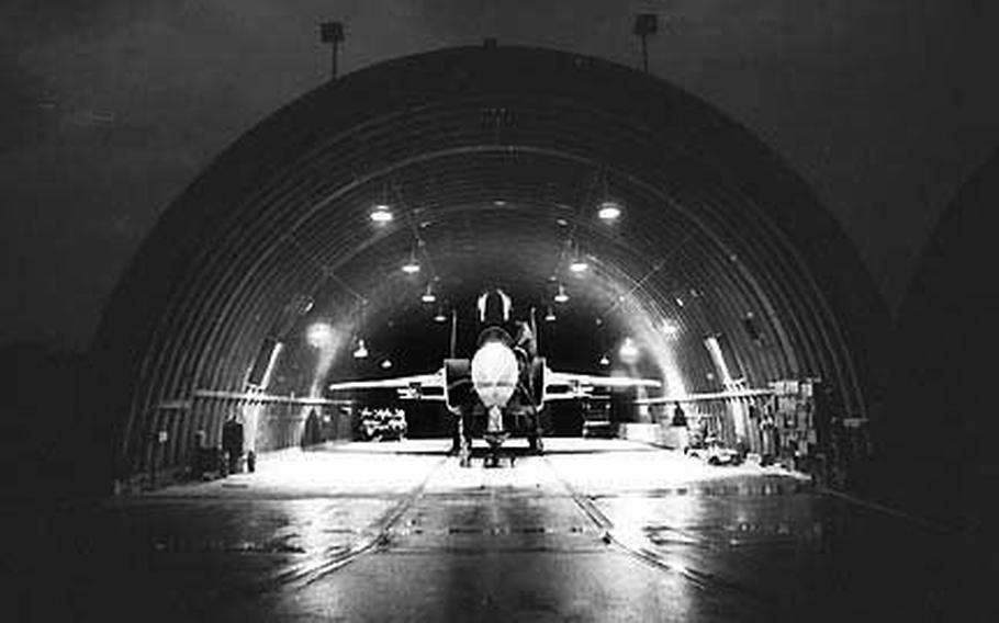 Staff Sgt. Edwin L. May and Airman Linnon Lathan work on an F-15 in the hangar at Bitburg Air Base, Germany, in November, 1979.