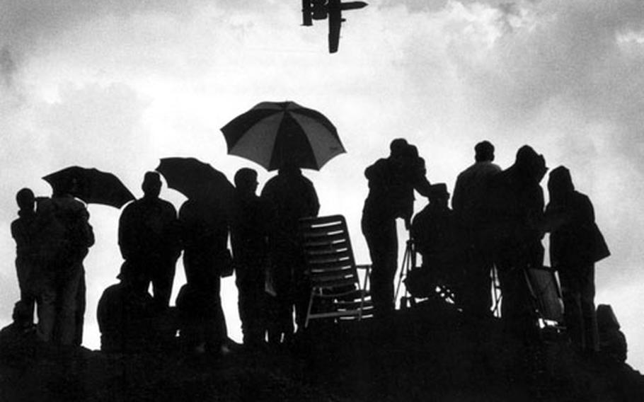 An A-10 anti-tank attack plane flies over spectators huddled under umbrellas near the runway during the annual Flugtag open house day at Ramstein Air Base in June, 1985.