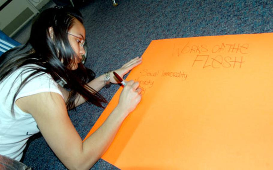 """Sophomore Angelique Tetrault makes a poster listing """"Works of the Flesh"""" during a discussion Wednesday during Videos, Inspiration and Pizza (VIP) at Misawa."""