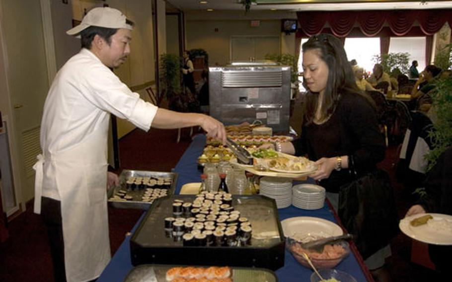 A Japanese employee serves food at the Enlisted Club at Yokota Air Base. On April 21 Yokota will merge its services and mission support squadrons into a new unit known as the 374th Force Support Squadron.