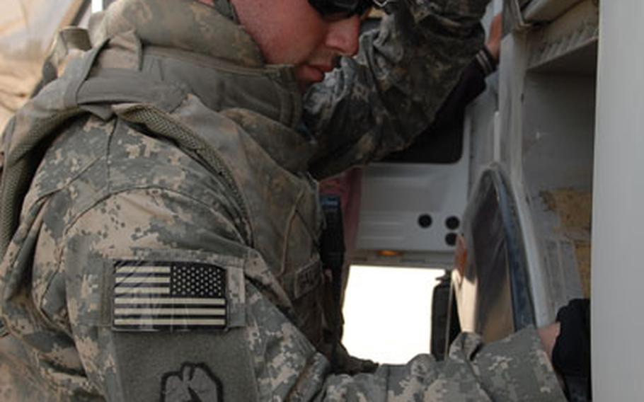 Pfc. Gregory Galarneau, 20, of San Antonio, Texas, checks inside a compartment on a civilian truck entering Camp Taji, Iraq, on Saturday. While the job is not directly related to Galarneau's official job as an artilleryman, he said he's enjoying how this new job lets him interact with Iraqi citizens.