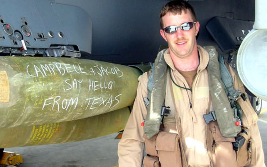 Capt. David Armitage, an F-15E weapons officer with the 48th Fighter Wing's 492nd Fighter Squadron at RAF Lakenheath, poses with an aircraft carrying a personal greeting during the early stages of the Iraq war, more than five years ago.