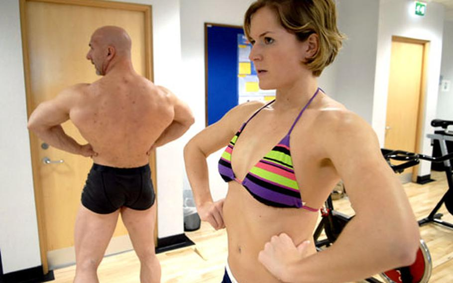Professional body builder John Wales, a personal trainer at RAF Lakenheath, instructs 1st Lt. Kathryn Swenson on poses she must execute for the Ultra Bodies contest in June at RAF Mildenhall.