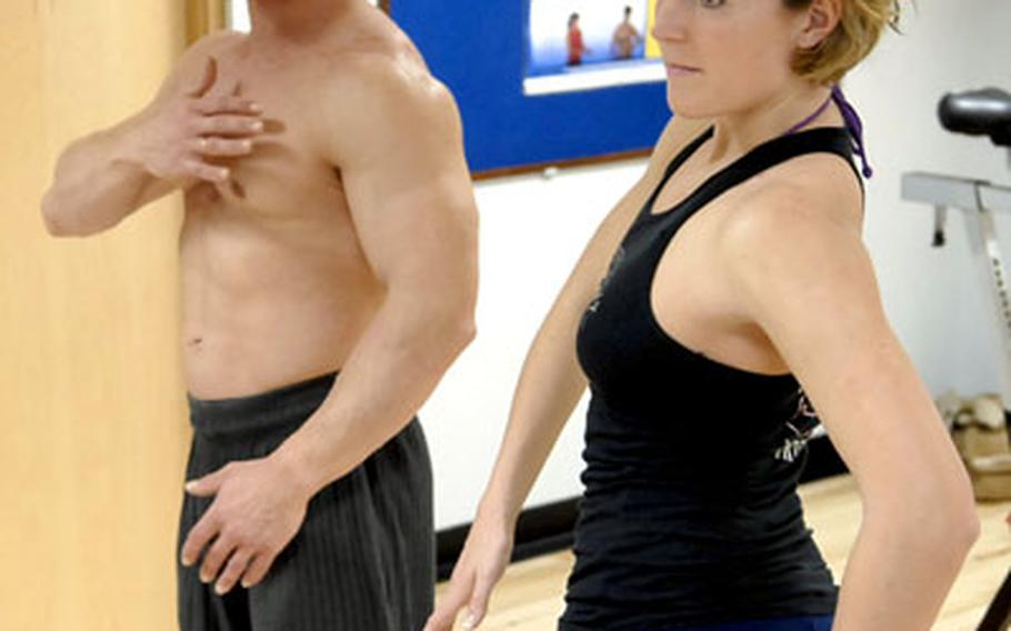 John Wales instructs 1st Lt. Kathryn Swenson on poses she must execute for the Ultra Bodies contest.