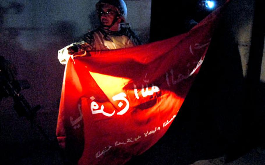 """John Issa, an interpreter who's an American citizen originally from Lebanon, translates words on a Shiite flag found Monday night in the Hurriyah area of Baghdad in a home once used as a kidnappers' hide-out. The flag reads, """"Muqtada Sadr, savior of god,"""" a reference to the Shiite cleric who heads the Mahdi Army. Al-Sadr has asked his followers to march from Baghdad to Najaf on Wednesday."""