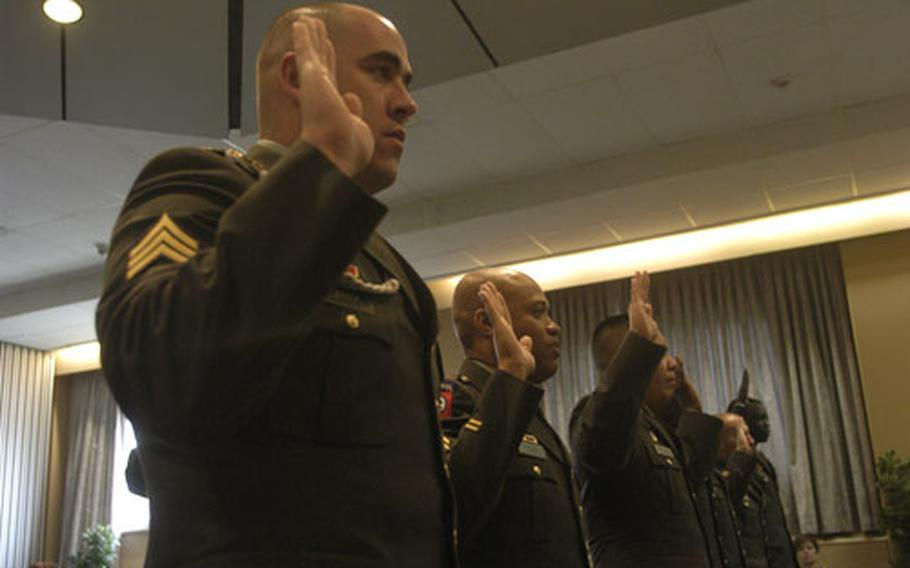 Irmak, front, and others take an oath on Wednesday as they became U.S. citizens during a ceremony in Stuttgart, Germany.