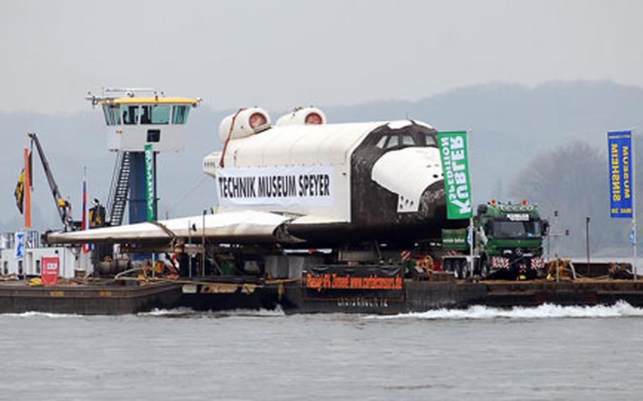 The Russian space shuttle Buran, loaded on a special transport, makes its way up the Rhine River to its new home at the Technik Museum in Speyer, Germany. Thousands have lined the Rhine to watch the shuttle.