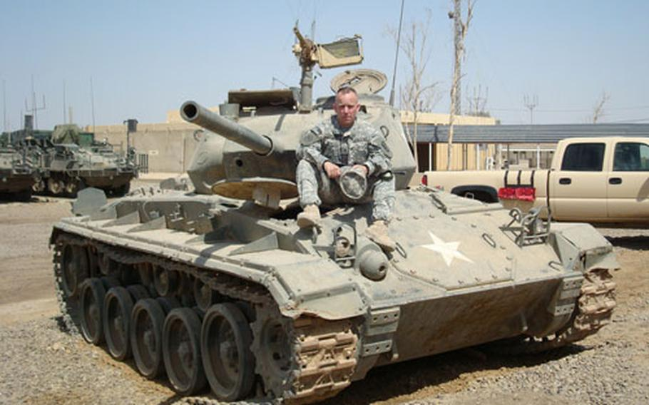 Staff Sgt. Kevin Corcoran of the California National Guard sits atop a World War II-era American tank on Camp Taji, Iraq, that he is trying to acquire for a California museum.