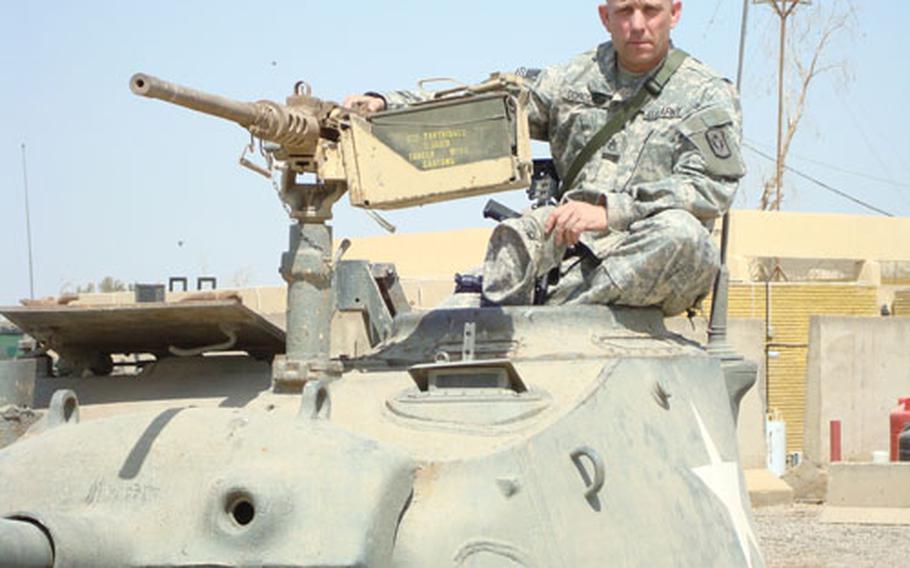 Staff Sgt. Kevin Corcoran of the California National Guard sits in the turret of a World War II-era American tank on Camp Taji, Iraq.
