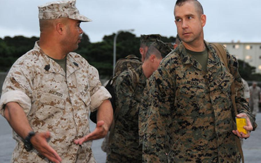 Master Sgt. Raymond Acevedo, left, with 12th Marines, 3rd Marine Division, welcomes Master Sgt. Delbert W. Meeker Jr., also with 12th Marines, back to Okinawa Wednesday after a nine-month deployment to Afghanistan. More than 80 division Marines returned Wednesday from the deployment where, as part of embedded training teams, they advised the Afghan National Army.