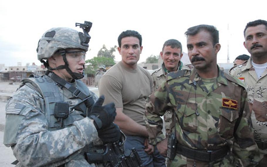 """Second Lt. Chris Pees, a platoon leader with Company A, 1st Battalion, 502nd Infantry Regiment, chats with Iraqi army Sgt. Jasim Hamadi about the situation in the Hurriyah neighborhood of Baghdad. Shiite criminal groups have been demanding """"security money"""" from fellow Shiites."""