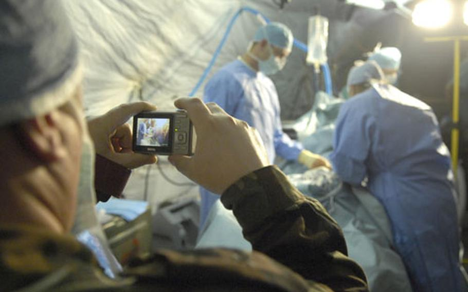 A doctor with the Moldovan military takes photos of Spc. Matthew Ruble, left, an operating room tech, and Dr. (Maj.) Elena Antedomenico during a medical procedure Tuesday.