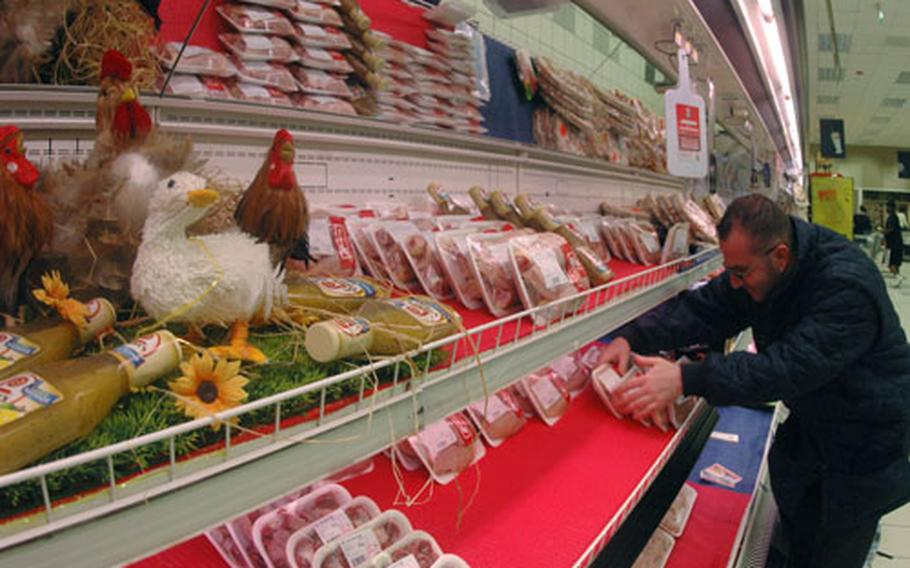 Nino D'Aloi adjusts fresh chicken packages in the commissary at the support site base in Naples, Italy, after a delivery Tuesday. Delivery of fresh chicken was suspended in February after inspection of the processing plant found coliform bacteria in water used to clean chickens after they are gutted.