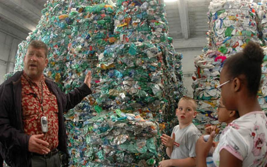Tim O'Connell, facilities director of government housing for Naval Support Activity Naples, explains to Naples Elementary School students on Tuesday how the Erreplast recycling plant separates plastics by color.