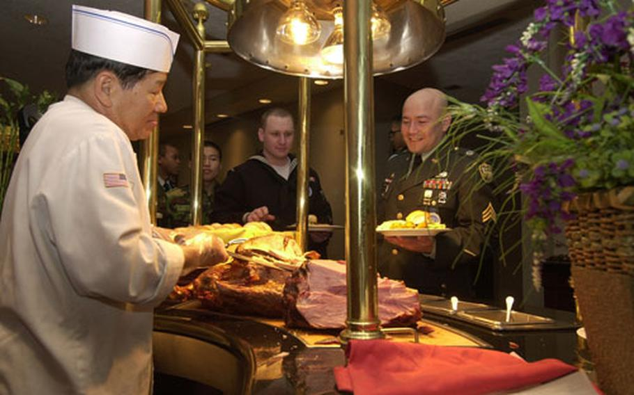 """U.S. Army Sgt. Cesar Alvarado, who serves with the United Nations Command's Military Armistice Commission, waits for a serving of turkey during the USO's 37th annual """"Six Star Salute"""" on Thursday at Yongsan Garrison, South Korea. Alvarado was one of 80 troops from across the peninsula selected for the two-day program."""