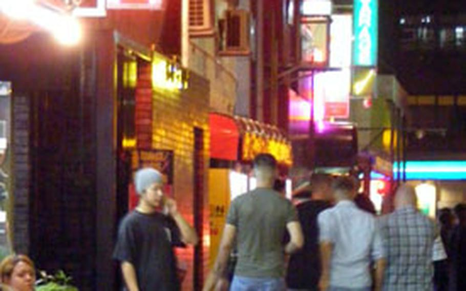 U.S. servicemembers make the rounds of bars on Gate Two Street in Okinawa City on Friday night. It was the first weekend in two months they were allowed to consume alcohol outside U.S. bases.