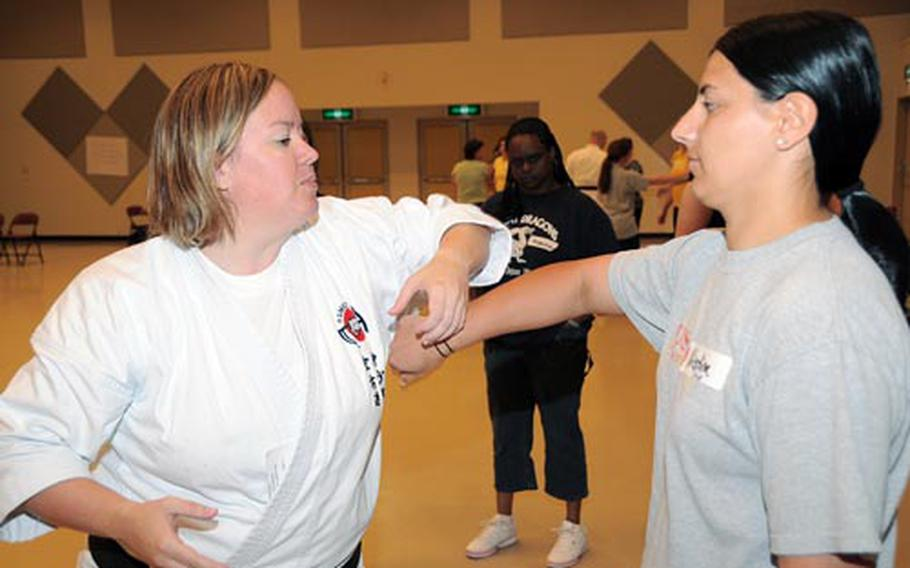 Joan Bade, left, a second degree black belt with the Okinawa Shorin-Ryu Matsumura Seito Karate and Kobudo Federation, demonstrates self-defense techniques to Kristine Costodio, a Marine spouse, at an Assertive Skills and Self Defense Workshop Saturday at the Performing Arts Center on Camp Foster. Two Criminal Investigations Division agents also taught self-assertiveness to approximately 40 women present at the workshop.