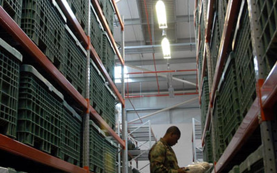 Airman 1st Class Perry Guinn examines some gear stored inside the 48th Logistics Readiness Squadron's deployment center warehouse last week.