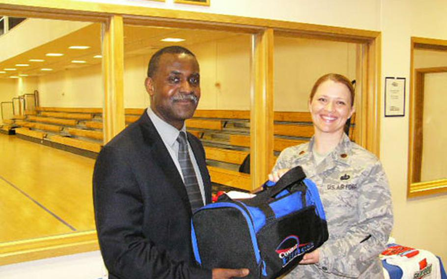John Randolph, winner of the 2008 Biggest Loser contest at RAF Mildenhall, receives a gym bag from Maj. Tammy Hinskton, commander of the 100th Services Squadron, last week.