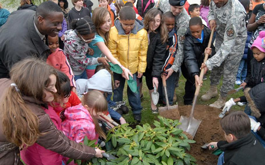 Darmstadt Elementary/Middle School students plant a rhododendron for Earth Day, with the help of principal Joseph Malloy, left, garrison commander Lt. Col. David Astin and Command Sgt. Maj. Harold Littlejohn, in front of the school on Tuesday. It is the final Earth Day celebration at the school that is closing at the end of the academic year.