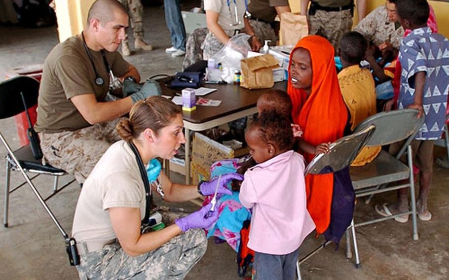Army Sgt. Catherine Olivarez takes a boy's temperature during a joint U.S. military medical team visit to the village of Goubetto, Djibouti, in March. As U.S. troops spend more time in Africa, they must be on the lookout for all the diseases on the continent, such as malaria and meningitis.
