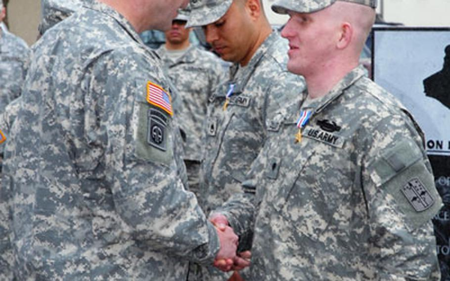 Spc. Jarrod Taylor, right, an infantryman with the 172nd Separate Infantry Brigade in Schweinfurt, Germany, shakes hands with 172nd commander, Col. Jeffrey Sinclair, after being decorated with the Silver Star at his battalion headquarters Tuesday. At center is Staff Sgt. Octavio Nuñez, who, like Taylor, was decorated Tuesday for heroic actions in Baghdad last May.