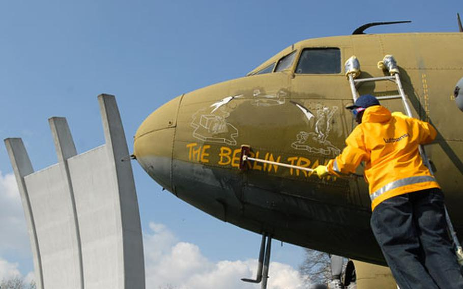 Staff Sgt. Federico Hudson cleans the C-47 Skytrain, one of two planes that are part of the Berlin Airlift Memorial at Frankfurt International Airport. At left is the monument, a twin of the one at Berlin's Templehof airport.