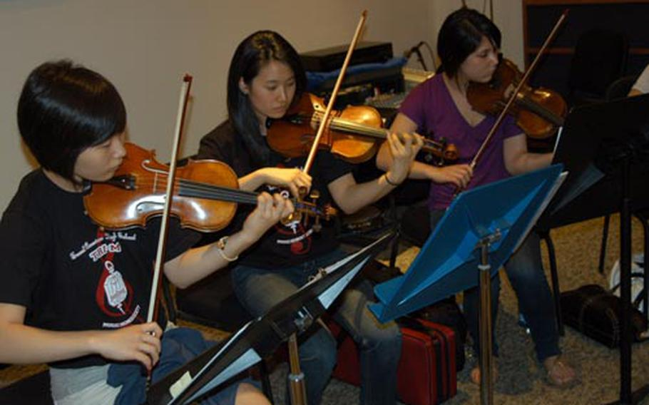Violin players, from left, Gina Lee, Esther Kim and Ava Burtch, all of Seoul American High School, rehearse with the nine-piece string ensemble.