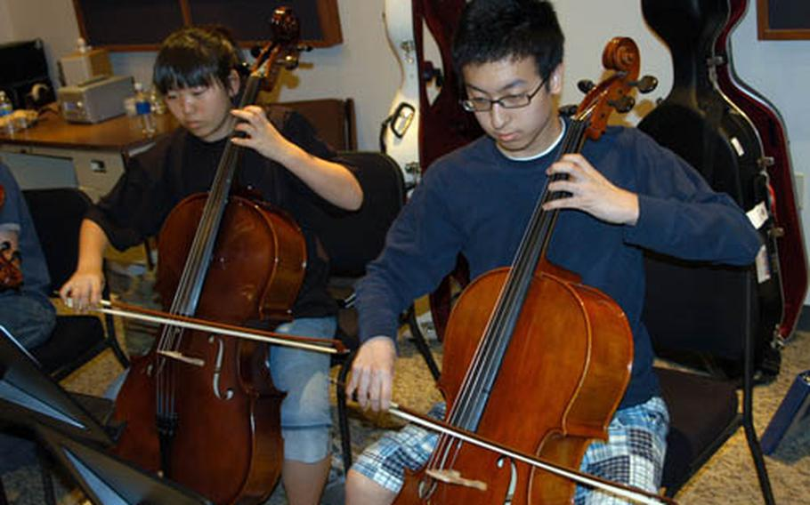 Cello players Yujin Chung, left, and Lucas Jung, both of Seoul American High School, rehearse with the nine-piece string ensemble Wednesday during the Far East Honor Music Festival at Yokota Air Base, Japan. The group is preparing for a concert finale on Friday.