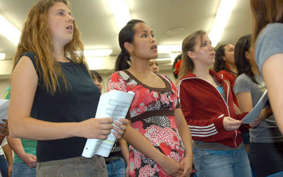 From left, Vanessa Ellis and Lisa Miyagi, both of Kubasaki High School, and Zama American's Madelyn Boatright rehearse with the Far East Honor Music Festival choir Wednesday at Yokota Air Base, Japan. The 80-member group is preparing for a concert finale on Friday.