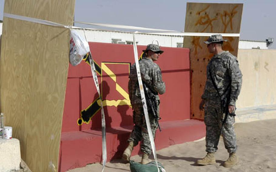 Solders with the 4th Battalion, 27th Field Artillery Regiment leave their mark at Camp Buehring, Kuwait, where hundreds of unit logos and mottos decorate the roadside walls.