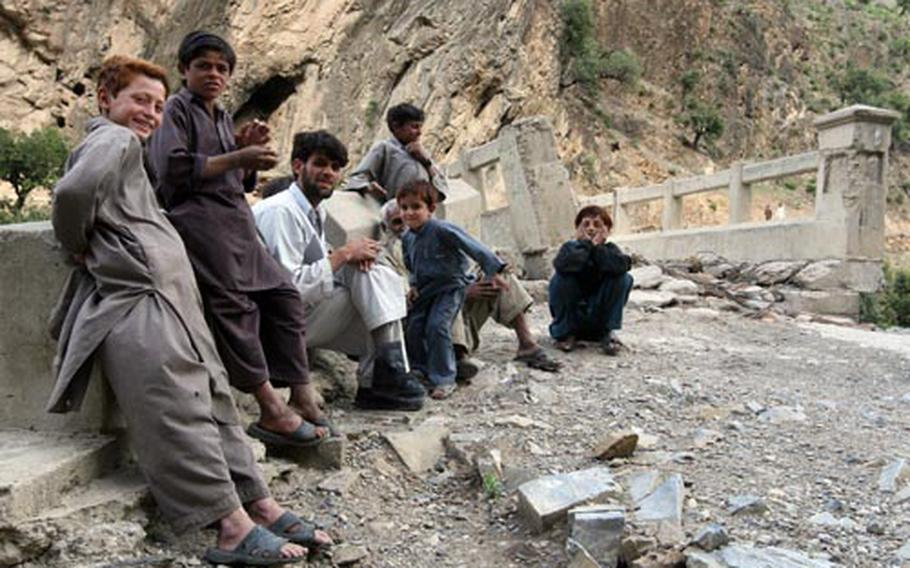Two Afghan men and a group of boys gather at the Gowerdesh Bridge after U.S. and Afghan government troops had taken control of it.