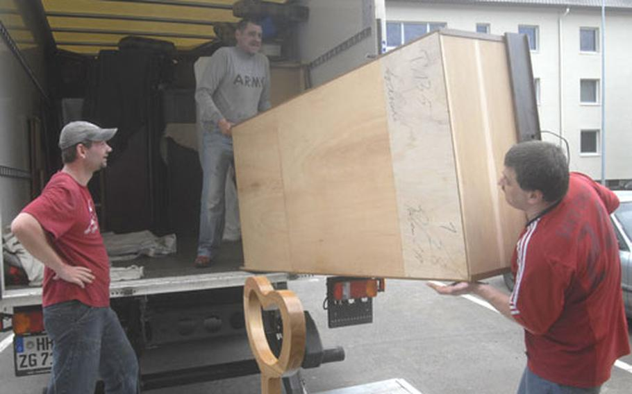 German movers Marcus Clemens, right, and Udo Kiktenko guide a piece of Army Sgt. Melisa Hall's furniture onto a moving truck Thursday as fellow mover Mario Leonhard catches his breath. Hall is one of 77 families in housing on the Landstuhl Regional Medical Center post that are being forced to move out of eight buildings to make way for incoming reservists.
